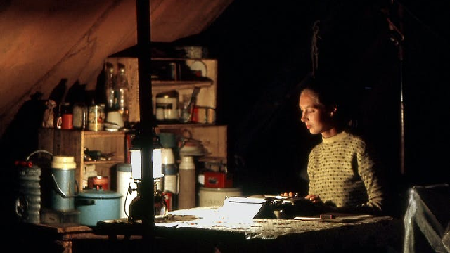 A young Jane Goodall writing up field notes in the dark in a tent in Gombe