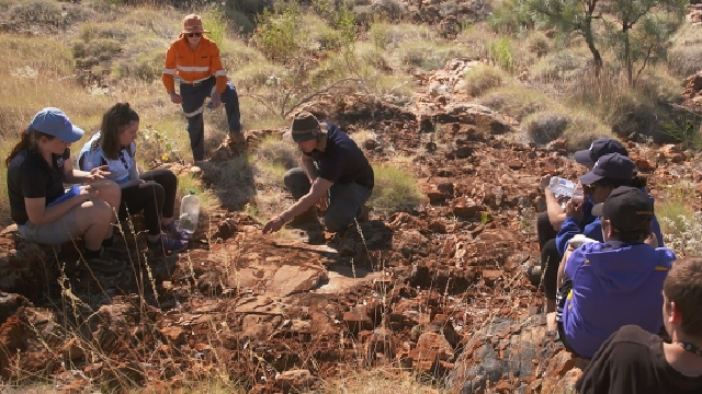 Students in Pilbara crouched looking for ancients signs of life and fossils