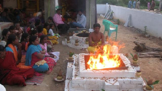 A man sits at a rectangular fire altar