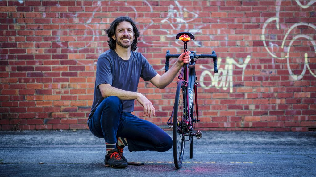 Tim Ottaway posing with his Project Flock bike light attached to a bike