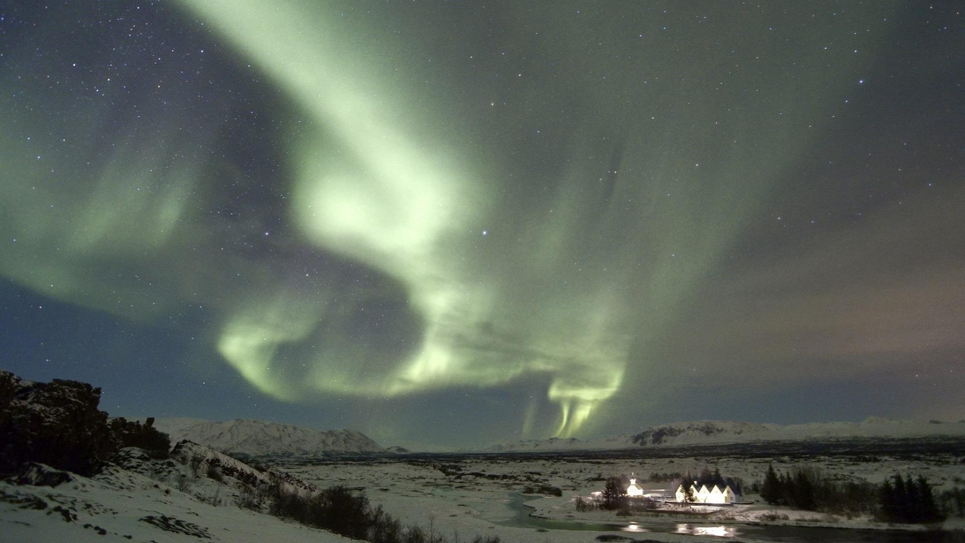Aurora borealis over snowy village at night