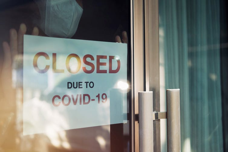 """Poster in a window saying """"Closed due to COVID-19"""""""