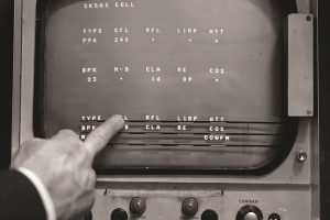 Black and white screen of air traffic control radar with finger pressing touchscreen
