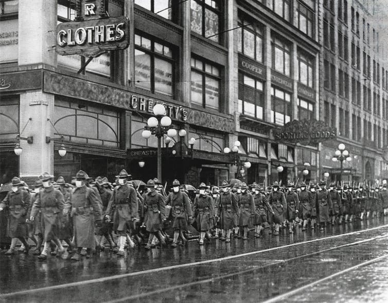 Black and white image of hundreds of people marching in the streets wearing protective masks.