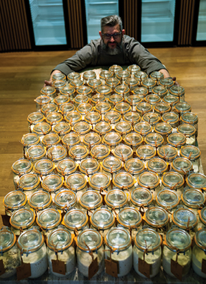 Sourdough librarian Karl De Smedt with his arms around some jars of his sourdough starter collection.