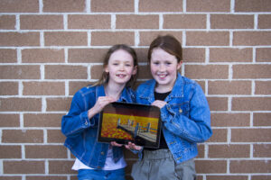 Two young girls in denim jackets holding a tablet showing the film they submitted and won a Eureka Prize.